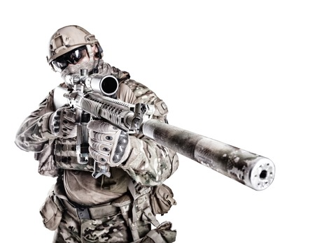 Half-length low angle studio shot of a big muscular soldier in field uniforms with the sniper rifle, portrait isolated on a white lot of copy space. Protective goggles glasses are on