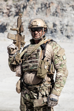 Half length location shot of big muscular soldier in field uniforms with rifle in the desert among rocks