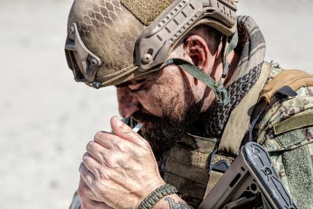 Closeup shot of smoking soldier in the desert among rocks Imagens