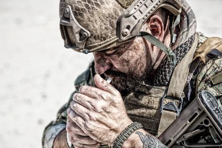 Closeup shot of smoking soldier in the desert among rocks Stock Photo