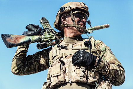 Half length low angle location shot of special forces soldier in field uniforms with weapons, portrait on blue sky background
