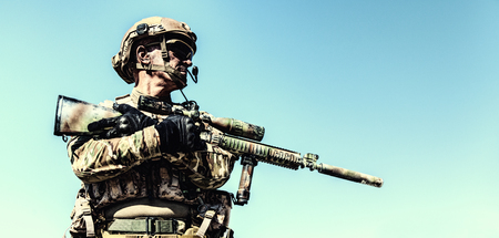 Half-length low angle location shot of special forces soldier in field uniforms with weapons, portrait on blue sky