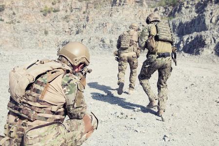 岩の間の砂漠でアクションの特殊部隊のチーム代表 写真素材