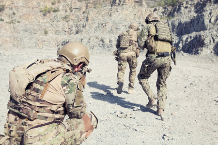 Team squad of special forces in action in the desert among the rocks Stock Photo