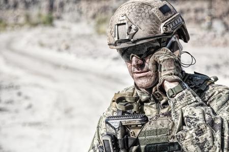 바위 가운데 사막에서 군인 calliong 전화의 근접 촬영 총 스톡 콘텐츠 - 92360974
