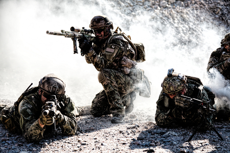 Team squad of special forces in action in the desert among the rocks covered by smoke screen