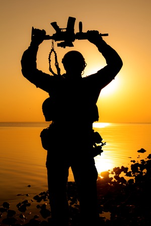 Army soldier with rifle above his head sunset silhouette. Victory concept