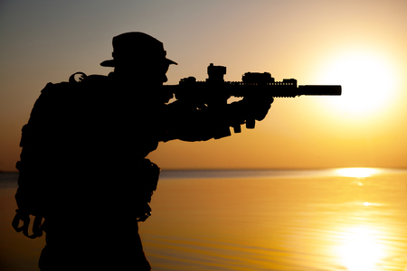Army soldier with rifle orange sunset silhouette Banco de Imagens