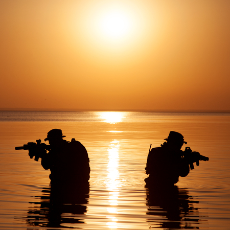 Army soldiers with rifles orange sunset silhouette in action during raid crossing river in the water