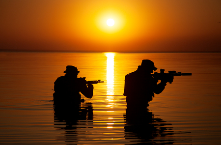 Army soldiers with rifles orange sunset silhouette in action during raid crossing river in the water Stock Photo - 90422394