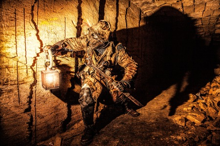Underground post apocalyptic creature with homemade weapons and lantern Reklamní fotografie - 89278610