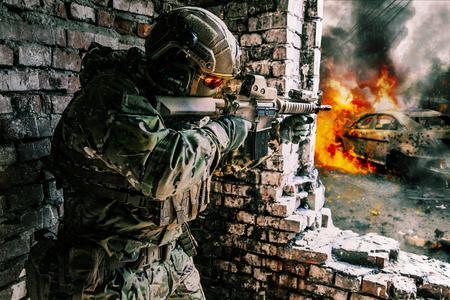 육군 병사가 파괴 된 건물에서 행동했다.
