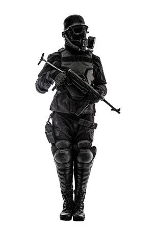 Futuristische nazi-soldaat schildwacht gasmasker en stalen helm met schmeisser pistool op wit wordt geïsoleerd studio shot staande op aandachtsprofiel