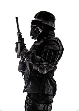 Het futuristische gasmasker van de militairschildwacht en staalhelm met schmeisserpistool op wit geschoten studioschot status aan aandachtsprofiel