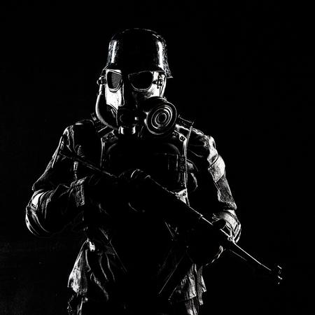 Masque à gaz soldat nazi futuriste et casque en acier avec une arme de poing schmeisser, fond noir, tourné en studio Banque d'images