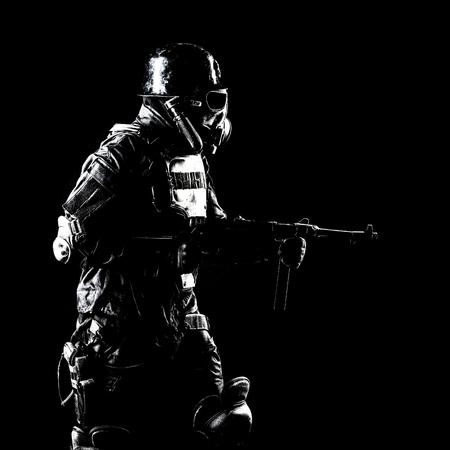 Futuristic soldier gas mask and steel helmet with schmeisser handgun black background studio shot