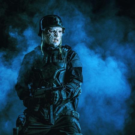 ガスマスクとスチールヘルメットで未来的なナチスの兵士の醜い顔。原子炎で焼かれた皮膚