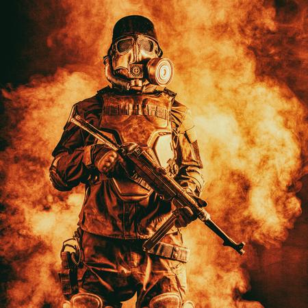 Futuristic soldier in fire and smoke gas mask and steel helmet with schmeisser handgun