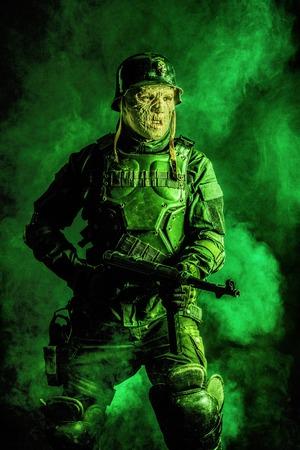 防毒マスクおよび鋼鉄ヘルメットの未来的なナチ兵士の醜い顔。原子の炎によって燃やされた皮