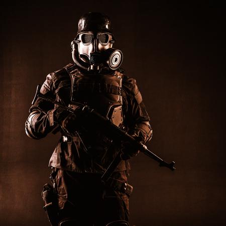 Masque à gaz soldat nazi futuriste et casque en acier avec une arme de poing schmeisser, fond noir, tourné en studio