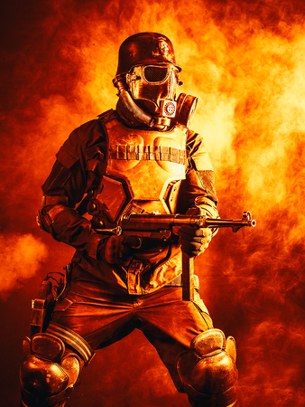 Futuristic nazi soldier in fire and smoke gas mask and steel helmet with schmeisser handgun Reklamní fotografie