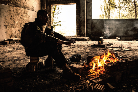 Special forces soldier after the fight sitting by the fire in ruined building warming his hands