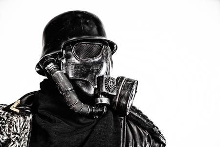 Futuristisch militairgasmasker en staalhelm met schmeisserpistool op wit studio geschoten close-upportret dat wordt geïsoleerd