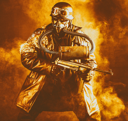 Futuristic  soldier in fire and smoke gas mask and steel helmet with  handgun Stock Photo