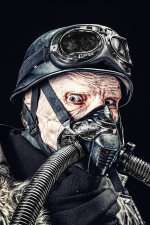Ugly face of Futuristic soldier in gas mask and steel helmet. Skin burned by atomic flame