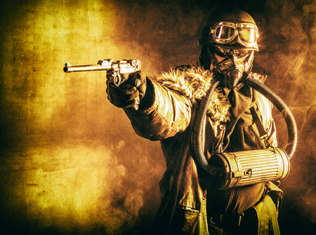 Futuristic nazi soldier in fire and smoke gas mask and steel helmet with luger pistol handgun Reklamní fotografie