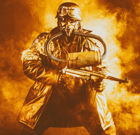 Futuristic  soldier in fire and smoke gas mask and steel helmet with  handgun Reklamní fotografie