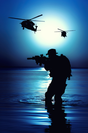 Army soldier with rifle night moon silhouette under cover of darkness in action during raid crossing river in the water.