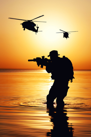 Army soldier with rifle sunset silhouette in action during raid crossing river in the water. Combat helicopters are supporting operation from air