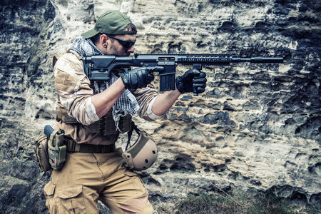 Private military contractor PMC in baseball cap with assault rifle in the rocks Stock Photo