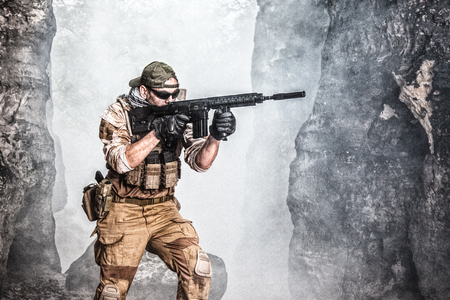 Private military contractor PMC in baseball cap with assault rifle in the rocks Stok Fotoğraf