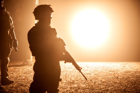 Black silhouette of soldier at night. Back light, cropped, toned and colorized