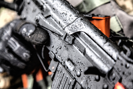 Close-up shot of rifle automatic weapons in hands of army special forces soldier under the rain Stock Photo