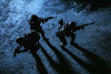 Black silhouette of soldiers at night. View from above, toned and colorized. Squad in action