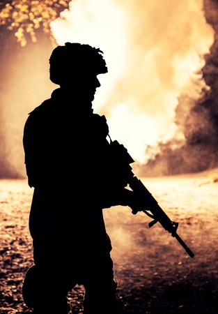 Black silhouette of soldier in the smoke moving in battle operation. Back light, cropped, toned and colorized Фото со стока - 96002696