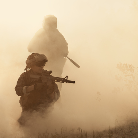 United States Marines in action. Military equipment, army helmet, warpaint, smoked dirty face, tactical gloves. Military action, desert battlefield, smoke grenades Stock fotó - 99912791