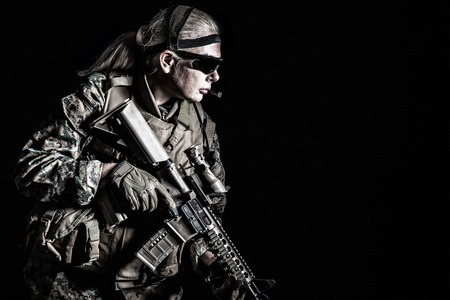 Foto de estudio de la Marina de los Estados Unidos con armas de fusil en uniformes. Equipo militar, casco militar, botas de combate, guantes tácticos. Aislado en negro, armas, ejército, concepto de patriotismo