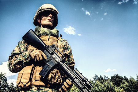 Location shot of United States Marine with rifle weapons in uniforms. Military equipment, army helmet, warpaint, smoked dirty face, tactical gloves. Weapons, army, patriotism concept Stock Photo