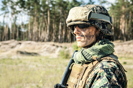 Location shot of United States Marine with rifle weapons in uniforms. Military equipment, army helmet, warpaint, smoked dirty face, tactical gloves. Weapons, army, american pride, patriotism concept Stock Photo