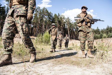 Location shot of United States Marine with rifle weapons in uniforms. Military equipment, army helmet, warpaint, smoked dirty face, tactical gloves. Military action, battlefield