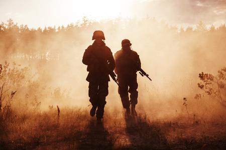 Marines Stanów Zjednoczonych w akcji. Sprzęt wojskowy, hełm wojskowy, farba wojenna, wędzona brudna twarz, rękawice taktyczne. Akcja wojskowa, pustynne pole bitwy, granaty dymne