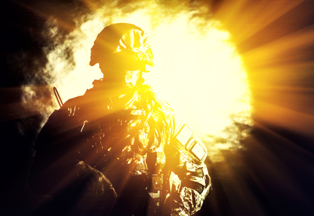 Low key studio portrait of private security service contractor, army infantry rifleman, US marine raider in blinding light of projector or searchlight in helmet, sunglasses, camouflage uniform posing with weapon on black background with backlight