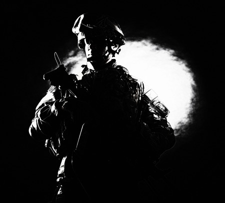 Low key studio portrait of private security service contractor, army infantry rifleman, US marine raider in helmet, sunglasses, camouflage uniform posing with weapon on black background with backlight