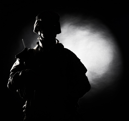 Silhouette photo of army soldier, modern combatant, military conflict participant standing in combat uniform with fiery spot on black background. Fire of war, ashes of battle, nuclear fire concept Stock Photo