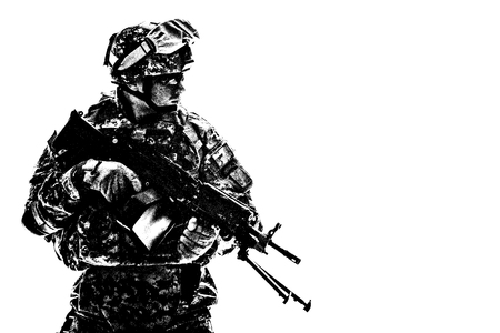 Low key side portrait of US Army Special Forces soldier in military camouflage uniform protected with helmet, body armour, holding machine gun desaturated, isolated on white background with copyspace