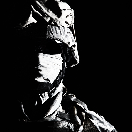 Close up portrait of modern infantry soldier, active army fighter, military mercenary in helmet, face hidden with balaclava and glasses high contrast, cropped on black background. Hybrid war concept Banque d'images - 101873451